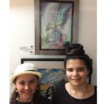 a photo of a young girl standing beside the student artist infront of the painting she has just bought