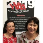 tow women teachers pose in front of the YYAA poster
