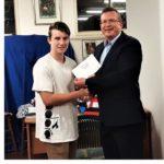 young man receiving an award from a local councillor
