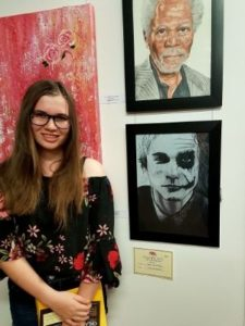 a teenage girl standing with her two portrait entries