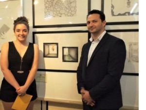 A teenage girl and a man standing beside her winning artwork