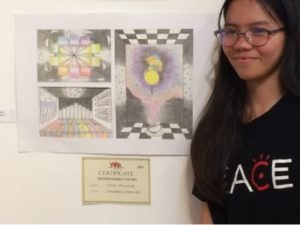 a teenage girl stands with her prize winning drawing