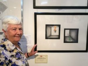 Sylvia Heterick stands beside the drawing that won the Major prize of the exhibition