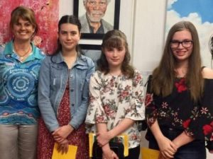 a local councillor standing with three teenage girls at the opening night