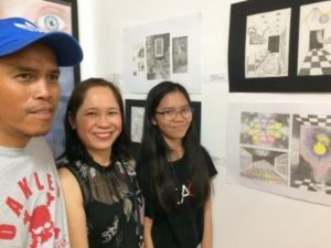 A father, mother and their teenage daughter pose beside the daughters artwork