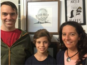 a young boy and his parents in front of his prize winning drawing of an old man
