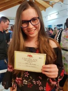 A teenage girl showing her award certificate